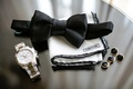 Tom Ford white pocket square with black border, black bow tie, silver watch, black cufflinks