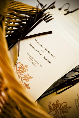 Wedding programs stamped with gold design in basket