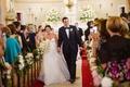 Bride in legends romona keveza wedding dress holding groom hand walking up aisle ceremony church