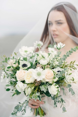 a bride holds a lush bouquet of green foliage surrounding white and blush flowers on a beach