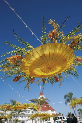 upside down parasols decorated with orchid blossoms hang above tables