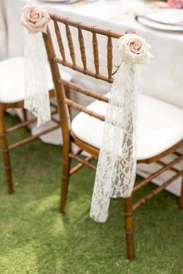 Bride to be chair decoration at outdoor bridal shower with lace fabric and pink roses