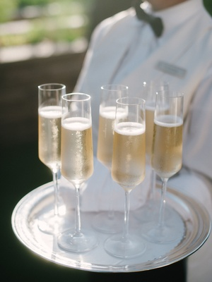 Wedding outdoor cocktail hour server with tray of full Champagne glasses