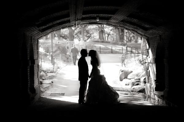 Black and white photo of couple under bridge