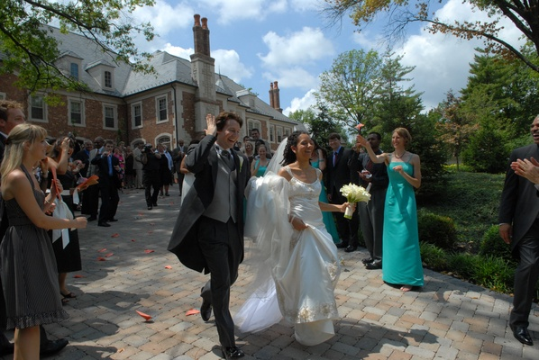 Bride in a Reem Acra gown with groom in black tails and grey vest exit ceremony
