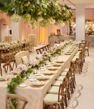 Rustic wedding ceremony greenery runner and chandeliers with hydrangea balls and greenery overhead