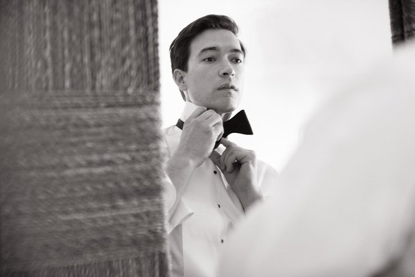 black and white photo of groom putting on his bow tie