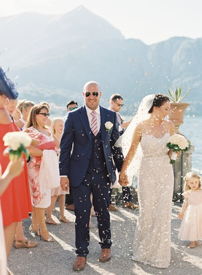 wedding guests tossing confetti flower petals as bride and groom arrive to reception venue lake como