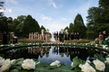wedding ceremony in front of pond decorated with split leaves and large white flowers