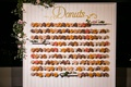 wedding reception desserts favors donut wall on sticks pegs shiplap pink flowers greenery