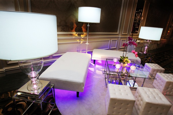 Wedding lounge area with modern white furnishings and purple lighting