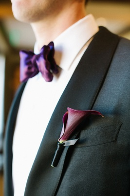 Wedding attire groom suit with calla lily boutonniere night cap and purple bow tie white shirt black