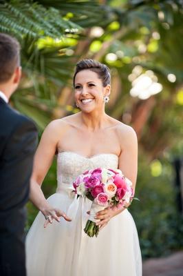 Bride in Monique Lhuillier wedding dress with pink bouquet
