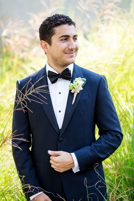 Groom in navy blue tuxedo jacket with black lapels buttons and bow tie natural boutonniere