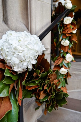 Stairs to Chicago church decorated with garland of magnolia leaves white hydrangea and rose flowers