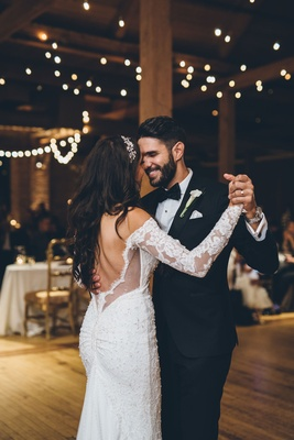 Bride and groom first dance rustic wedding twinkle lights lace long sleeves low back ruching tuxedo