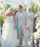 Bride in Maggie Sottero gown with groom in tan suit leave ceremony