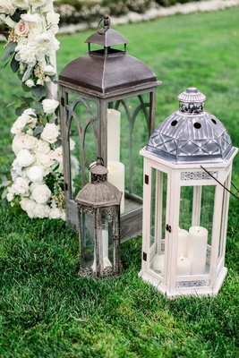 wedding ceremony outdoor grass lawn antique style candle lantern decor under ceremony arch flowers