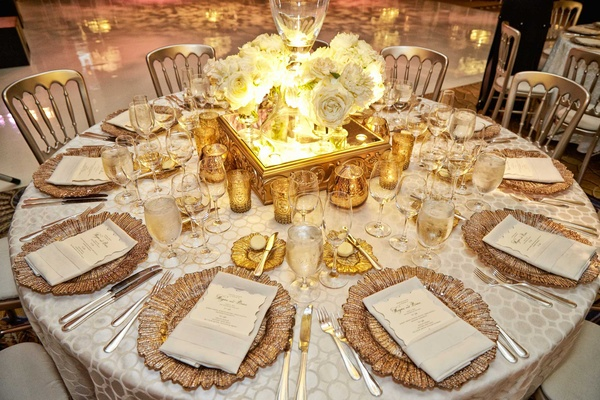 white detailed table linens with gold charger plates white menus small gold candles mirror stand