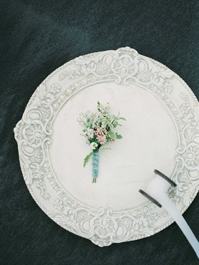 small muted boutonniere with green foliage and white flowers on a white charger plate