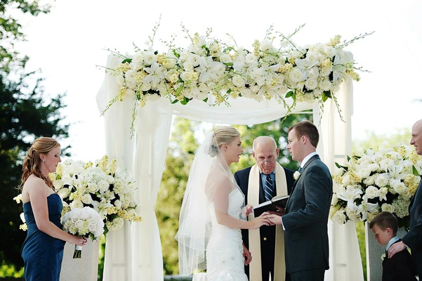 Bride and groom under canopy of white flowers