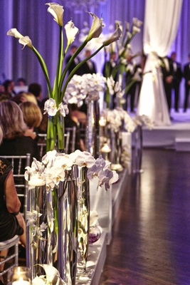 Tall glass vases along aisle filled with orchids and calla lilies