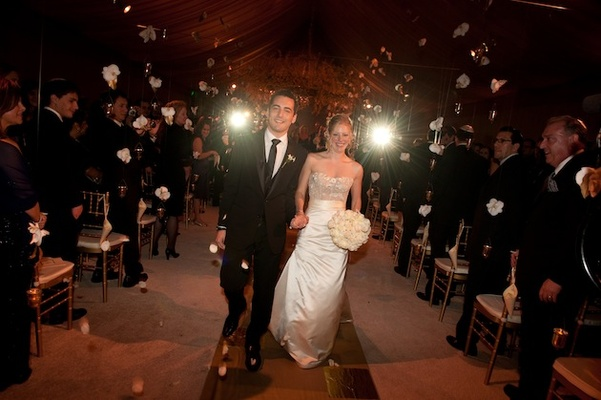 Bride and groom walk between strands of flowers