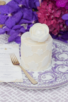 Personal white wedding cake with flower and leaf design topped with a sugar flower, on Versace plate