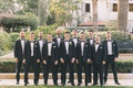 groom with 10 groomsmen in matching black tuxedos for palm beach wedding