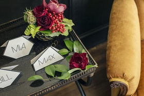 Wedding reception place cards in geometric forms on table with greenery red roses, orchids