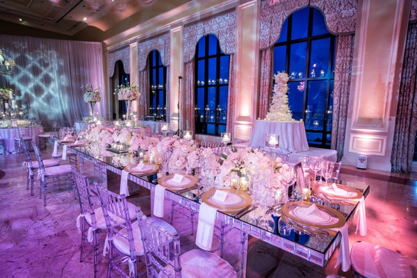 The Breakers wedding reception mirror table with gold chargers, low tulip rose hydrangea centerpiece