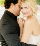 bride looks to the camera and smirks as the groom hugs her