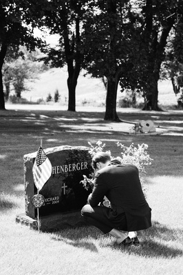 Black and white photo of groom at father of the bride's grave