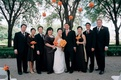 Bride in a strapless dress, groom in a black tuxedo, and bridal party dressed in a dark color