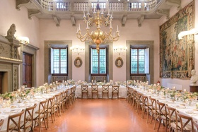 wedding reception villa ballroom u shape table low centerpieces tapestry chandelier vineyard chairs