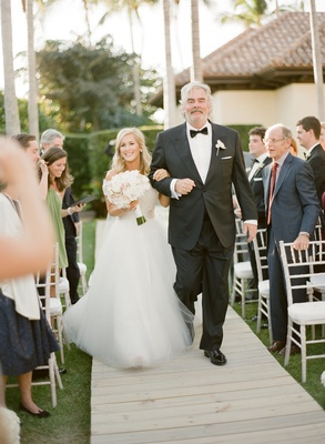 Bride in a Monique Lhuillier gown is walked down the aisle by her father in a black tuxedo
