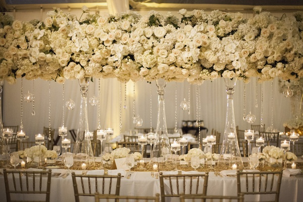 Wedding reception table with tall arrangements of white roses, hydrangeas, and orchids, crystals