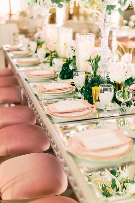 wedding reception long table mirror top with pink place settings low greenery pink velvet chairs