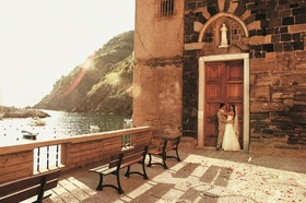 Bride and groom in front of church doors in Italy