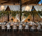 greenery displayed above king's table at wedding reception, drapery