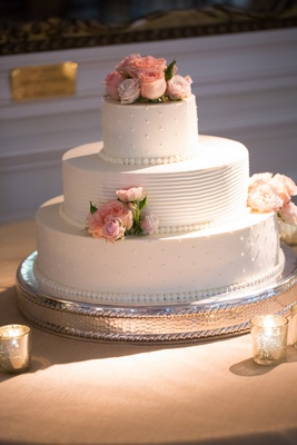 White wedding cake with Swiss dots and fresh pink roses on top