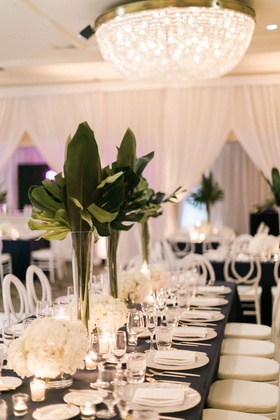 wedding reception chandelier rectangle table navy blue white hydrangea low centerpiece tall tropical