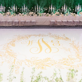 white dance floor with gold monogram surrounded by gold wreath