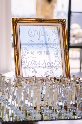 mirrored sign for escort cards, champagne flutes for guests