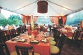 Tables covered in orange tablecloths and various bouquets in a reception tent