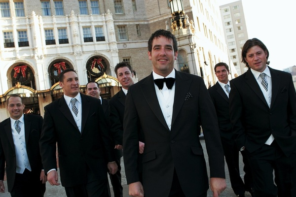 Groom with groomsmen in black tuxedos and striped ties