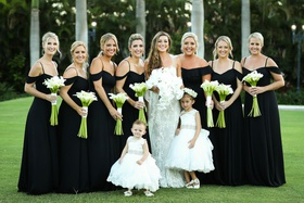 bride in monique lhuillier white lace wedding dress flower girls bridesmaids black gown off shoulder
