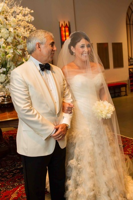 Bride smiles largely with father of the bride