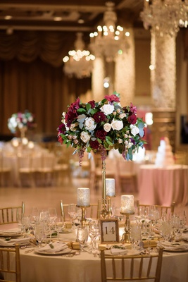 Round table gold riser flower arrangement burgundy green white chandeliers candlelight gold chairs