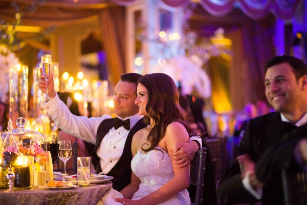 Groom holding up champagne glass next to bride